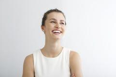 Ung kvinna som ler mot vit bakgrund royaltyfria bilder