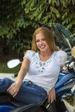 Ung kvinna som ler och poserar på en motorcykel Arkivbild