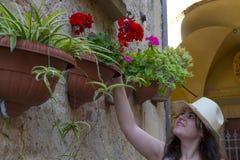 Ung kvinna som ler och ser blommor Royaltyfri Fotografi