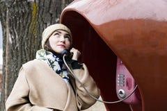 Ung kvinna som ler och talar på en offentlig telefon Royaltyfria Foton