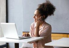 Ung kvinna som ler och talar på mobiltelefonen Arkivfoto