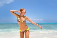 Ung kvinna som ler på stranden arkivfoto