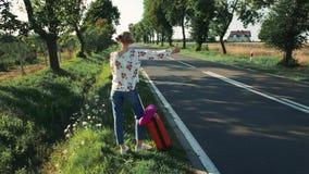 Ung kvinna som liftar på bygdvägen stock video