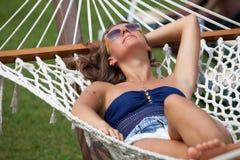 Ung kvinna som ligger i en hängmatta Arkivbild