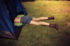 Ung kvinna som ligger i ett tält Fotografering för Bildbyråer