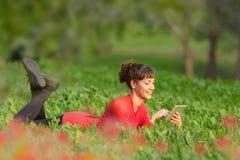 Ung kvinna som ligger i gräset med den digitala minnestavlan Royaltyfri Foto