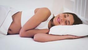Ung kvinna som ligger i säng med öppnade ögon och att le lager videofilmer