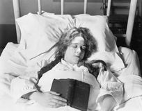 Ung kvinna som ligger i säng, sover och rymmer en bok (alla visade personer inte är längre uppehälle, och inget gods finns levera Royaltyfria Foton