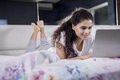 Ung kvinna som ligger med bärbara datorn på sängen royaltyfri bild