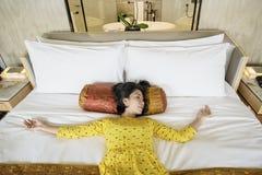 Ung kvinna som ligger på den lyxiga sängen Royaltyfri Bild