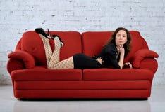 Ung kvinna som ligger på den röda soffan Royaltyfria Foton