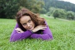 Ung kvinna som ligger på en grön gräsmatta Royaltyfria Foton