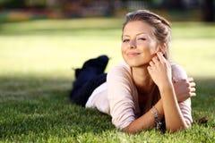 ung kvinna som ligger på en grön gräsmatta Arkivfoto