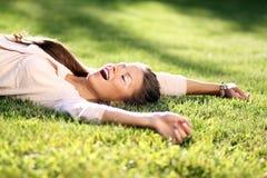 ung kvinna som ligger på en grön gräsmatta Royaltyfri Fotografi