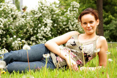 ung kvinna som ligger på en grön gräsmatta royaltyfri foto