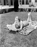 Ung kvinna som ligger på en handduk i hennes gård som solbadar och läser (alla visade personer inte är längre uppehälle, och inge Arkivfoto