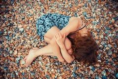 Ung kvinna som ligger på ett Pebble Beach Arkivbilder