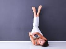 Ung kvinna som ligger på golvet med ben upp Royaltyfri Fotografi