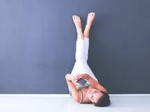 Ung kvinna som ligger på golvet med ben upp Royaltyfria Bilder