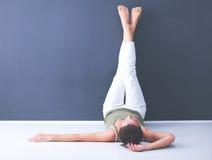 Ung kvinna som ligger på golvet med ben upp Arkivbilder