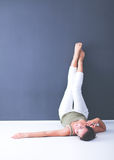 Ung kvinna som ligger på golvet med ben upp Arkivfoto