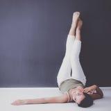 Ung kvinna som ligger på golvet med ben upp Fotografering för Bildbyråer