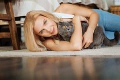 Ung kvinna som ligger på golvet med hennes katt royaltyfria bilder