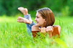 Ung kvinna som ligger på gräs Arkivbild