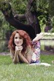 Ung kvinna som ligger på gräs Arkivfoto