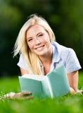 Ung kvinna som ligger på gräs och läseboken arkivfoton