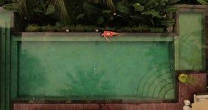 Ung kvinna som ligger på poolsiden stock video