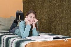 Ung kvinna som ligger på säng med boken Arkivbilder