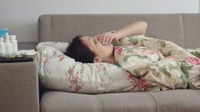 Ung kvinna som ligger på sängen med en hosta Arkivfoto