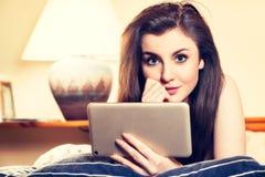 Ung kvinna som ligger på sängen och använder minnestavlan Royaltyfri Fotografi