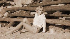 Ung kvinna som ligger på sand Arkivbilder