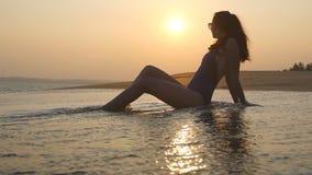 Ung kvinna som ligger på sandstranden och tvättar sig vid havvågor Gullig flicka som kopplar av på tropisk havskust på solnedgång arkivfilmer