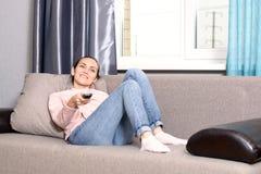 Ung kvinna som ligger på soffan med fjärrkontrollen av TV:N och håller ögonen på en film royaltyfria foton