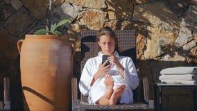 Ung kvinna som ligger på sunbed med telefonen i händerna lager videofilmer