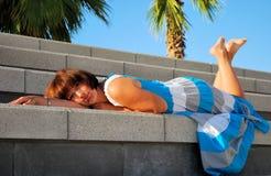 Ung kvinna som ligger på trappan Fotografering för Bildbyråer