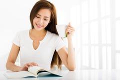Ung kvinna som läser en bok i vardagsrum Royaltyfria Foton