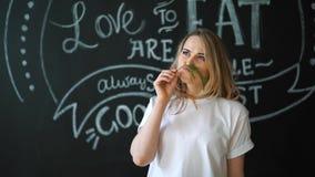 Ung kvinna som luktar den gröna dillsmaktillsatsgrönsaken Mustasch från fänkål roligt kök Begreppet av sunt stock video