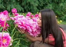 Ung kvinna som luktar en blommapion Royaltyfri Fotografi