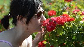 Ung kvinna som luktar röda blommor lager videofilmer