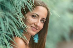 Ung kvinna som lutar mot det frodigt, turkosgräs på staketet, närbildstående royaltyfri fotografi