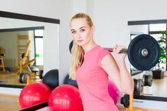 Ung kvinna som lyfter en skivstång i idrottshallen Fotografering för Bildbyråer