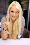 Ung kvinna som lyfter ett exponeringsglas av champagne royaltyfri bild