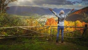 Ung kvinna som lyfter händer på bergsiktspunkt stock video