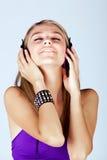 Ung kvinna som lyssnar till musik Arkivfoto
