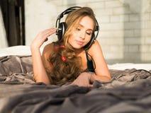 Ung kvinna som lyssnar till musik i hörlurar på säng Arkivbilder
