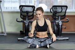 Ung kvinna som lyssnar till musik med hörlurar i idrottshallen Fotografering för Bildbyråer